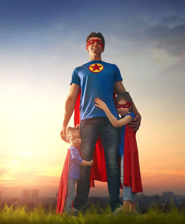 Happy loving family. Dad and his daughters are playing outdoors. Daddy and his children girls in an Superheros costumes. Concept of Fathers day. Stock Photo