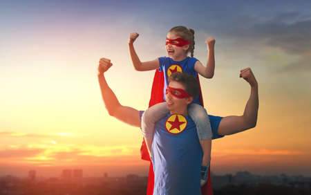 Happy loving family. Dad and his daughter playing outdoors. Daddy and child girl in an Superheros costumes. Concept of Fathers day.