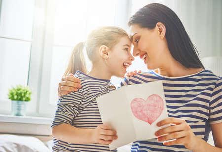 Gelukkige Moederdag! Child dochter feliciteert moeder en geeft haar briefkaart. Mama en meisje lachend en knuffelen. Vakantie met het gezin en saamhorigheid.