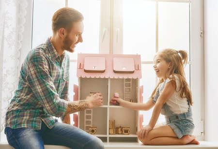 Gelukkig vader en dochter meisje spelen met poppenhuis thuis. Grappig mooi familie is plezier in de kinderkamer.