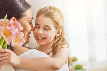 Happy mother's day! Child daughter congratulates mom and gives her flowers tulips. Mum and girl smiling and hugging. Family holiday and togetherness. Banque d'images