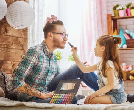 Funny time! Father and his child are playing at home. Cute girl is doing makeup to her dad, sitting on the bed in the bedroom. Family holiday and togetherness.