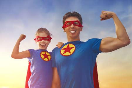 快乐幸福的家庭。爸爸和他的女儿在户外玩。爸爸和女儿穿着超级英雄的服装。父亲节的概念。