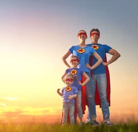 Mutter, Vater und ihre Töchter spielen im Freien. Mama, Papa und Kinder Mädchen in einem Kostüm des Superhelden. Konzept der Superfamilie.