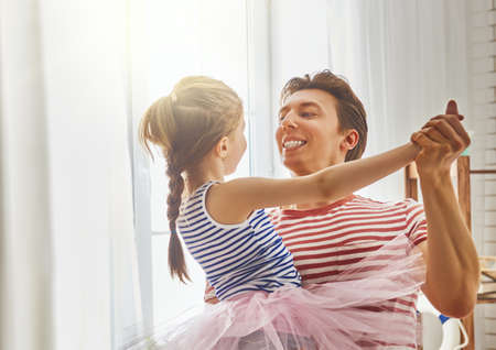 Happy fathers day! Dad and his daughter child girl are playing, smiling and dancing. Family holiday and togetherness.