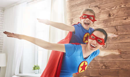 Mother and her child playing together. Girl and mom in Superhero costume. Mum and kid having fun, smiling and hugging. Family holiday and togetherness.