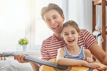 Happy fathers day! Dad and his daughter child girl are playing guitar together. Family holiday and togetherness. Stock Photo