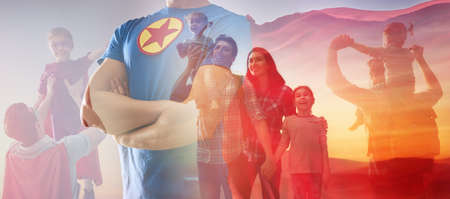 Concept of fathers day! Man in superhero costume is protecting his family.