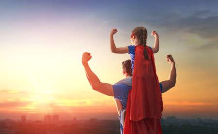 행복 한 사랑 가족. 아빠와 그의 딸이 야외에서 연주. 슈퍼 히어로의 의상 아빠와 아이 소녀. 아버지의 날의 개념. 스톡 콘텐츠