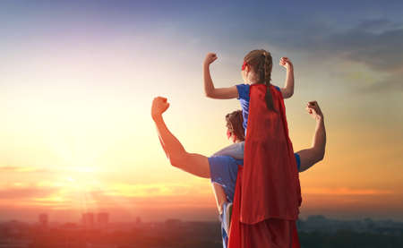 Happy loving family. Dad and his daughter playing outdoors. Daddy and child girl in an Superhero's costumes. Concept of Father's day. Imagens - 76828909