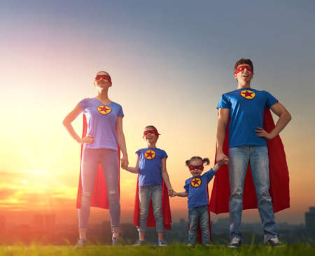 Mother, father and their daughters are playing outdoors. Mommy, daddy and children girls in an Superhero's costumes. Concept of super family.