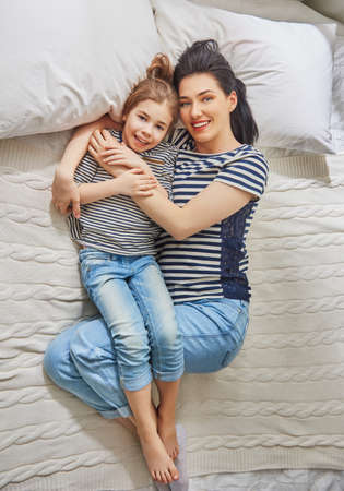 Happy mothers day! Mom and her daughter child girl are playing, smiling and hugging. Family holiday and togetherness.