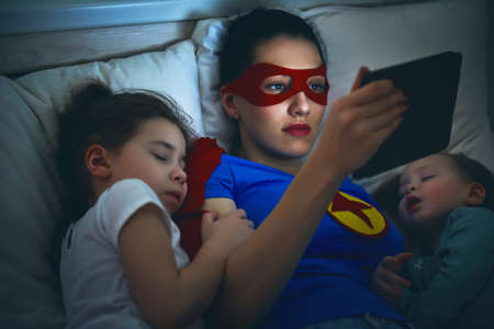 Schattige kleine kinderen meisjes zijn slapend in het bed met hun moeder. Rustig slapen met teddybeer onder de bescherming van de moeder superheld. Stockfoto