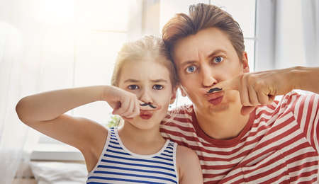 Happy father's day! Dad and his child daughter are playing and having fun together. Beautiful funny girl and daddy have mustache on fingers. Family holidays and togetherness.