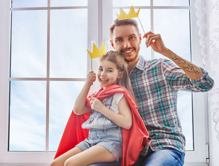 Happy fathers day! Dad and his child daughter are playing and having fun together. Beautiful funny girl and daddy have crowns on sticks. Family holidays and togetherness.