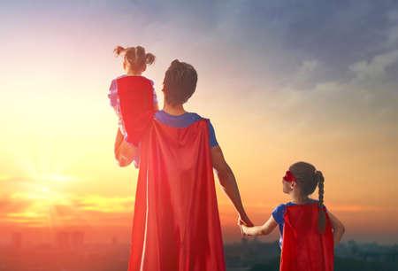 행복 한 사랑 가족. 아빠와 그의 딸이 야외에서 연주된다. 슈퍼 히어로의 의상을 입고 아빠와 자녀들 여자. 아버지의 날의 개념.