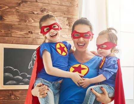 Mother and her children playing together. Girls and mom in Superhero costumes. Mum and kids having fun, smiling and hugging. Family holiday and togetherness. 스톡 콘텐츠
