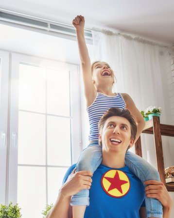 freedom: Father and his child playing together. Girl and dad in Superhero costume. Daddy and kid having fun, smiling and hugging. Family holiday and togetherness.