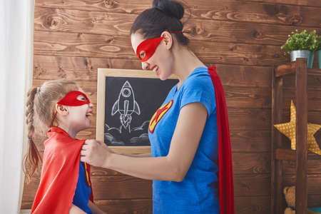 mommy: Mother and her child playing together. Girl and mom in Superhero costume. Mum and kid having fun, smiling and hugging. Family holiday and togetherness.