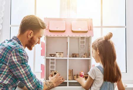 Gelukkig vader en dochter meisjesspel met poppenhuis thuis. Grappige mooie familie heeft plezier in de kinderkamer.