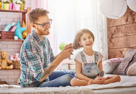 Gelukkige liefdevolle familie. Vader koestert haar dochter's haar op het bed in de kamer zitten. Stockfoto