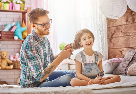 Happy loving family. Father is combing her daughters hair sitting on the bed in the room. Stock Photo