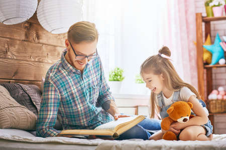 home: Father and child on the bed in kids room. Handsome young daddy reading a book to his daughter. Family holiday and togetherness.