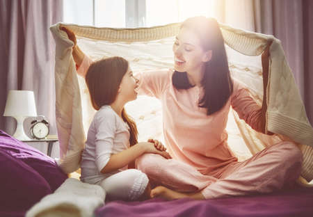 bedroom: A nice girl and her mother enjoy sunny morning. Good time at home. Child wakes up from sleep. Family playing under blanket on the bed in the bedroom. Stock Photo