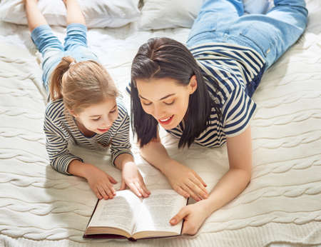 Pretty young mother reading a book to her daughter. Family holiday and togetherness. Stock Photo