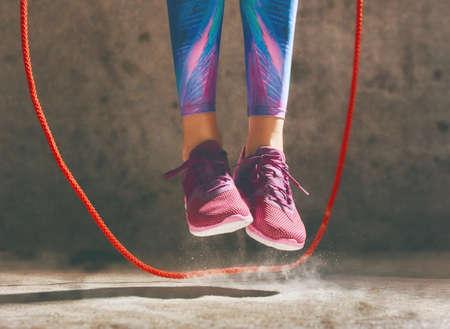 Gezonde levensstijl en sportconcepten. Vrouw in modieuze sportkleding doet oefening met een touwtje.
