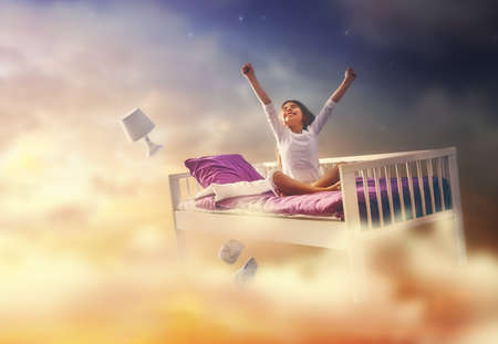 night vision: Kids dreams. Cute child girl is flying in her bed trough star sky. Stock Photo