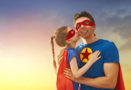 super dad: Happy loving family. Dad and his daughter playing outdoors. Daddy and child girl in an Superheros costumes. Concept of Fathers day.