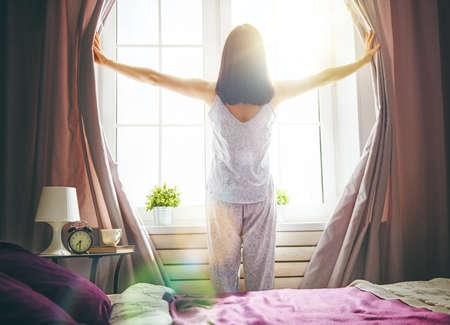 화창한 아침에 침대에서 행복 한 젊은 여자 즐기기. 스톡 콘텐츠