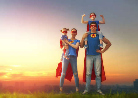 Mother, father and their daughters are playing outdoors. Mommy, daddy and children girls in an Superhero's costumes. Concept of super family. Reklamní fotografie - 77110098