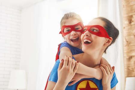 母と彼女の子供は一緒に遊ぶ。女の子とスーパー ヒーローの衣装のお母さん。ママし、子供の楽しい、笑顔、ハグします。家族の休日と一体感。