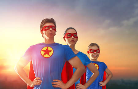 Mother, father and their daughter are playing outdoors. Mommy, daddy and child girl in an Superhero's costumes. Concept of super family. Stock Photo