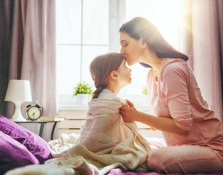 A nice child girl and her mother enjoy sunny morning. Good time at home. The mom wakes the kid with a kiss on the bed in the bedroom.