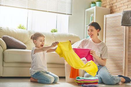 아름 다운 젊은 여자와 아이 소녀 작은 도우미 재미와 집에서 세탁을하는 동안 웃 고있다. 스톡 콘텐츠