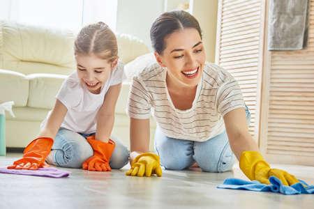 행복한 가족이 방을 청소합니다. 어머니와 딸이 집안 청소를합니다. 젊은 여자와 아이 소녀는 가루가. 귀여운 작은 도우미.