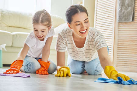 Happy family cleans the room. Mother and daughter do the cleaning in the house. A young woman and child girl are dusting. Cute little helper.