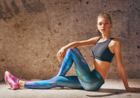 Healthy lifestyle and sport concepts. Woman in fashionable sportswear is doing exercise. Stock Photo