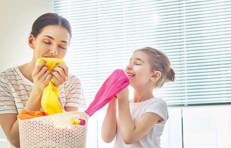아름 다운 젊은 여자와 아이 소녀 작은 도우미 깨끗 한 옷을 냄새 집에서 세탁을하는 동안 웃 고.