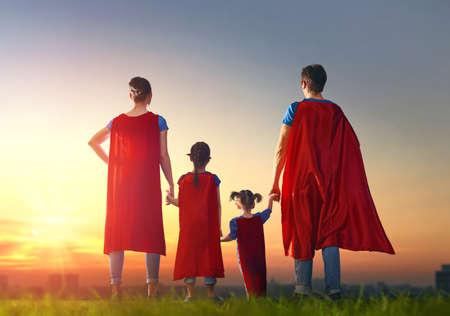 母と父と娘は屋外で遊んでいます。スーパー ヒーローの衣装のママ、パパと子供の女の子。スーパー家族の概念。