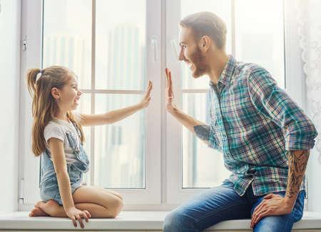 Glücklicher Vatertag! Dad und seine Tochter Kind Mädchen spielen, wrestling und lächelnd, während die Zeit zusammen zu Hause zu verbringen. Familienurlaub und Zusammengehörigkeit. Standard-Bild - 77784660