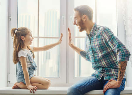 Happy father's day! Dad and his daughter child girl are playing, wrestling and smiling while spending time together at home. Family holiday and togetherness. 免版税图像