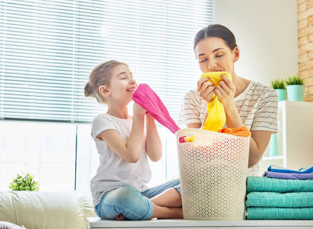 Beautiful young woman and child girl little helper are smelling clean clothes and smiling while doing laundry at home.