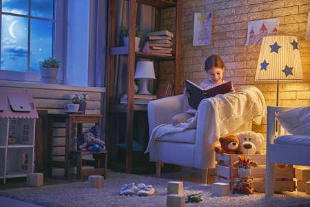 Nettes kleines Kind Mädchen, das ein Buch unter einer Lampe liest. Kind Mädchen sitzen im Sessel in der Nähe Fenster in einer dunklen mondhellen Nacht. Standard-Bild - 77881763