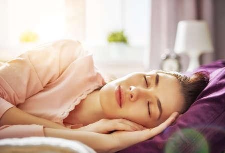 화창한 아침에 침대에서 자 고 행복 한 젊은 여자. 스톡 콘텐츠