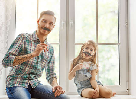 Happy fathers day! Dad and his child daughter are playing and having fun together. Beautiful funny girl and daddy have mustaches on sticks. Family holidays and togetherness.
