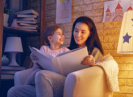 Familie, die Schlafenszeit liest. Hübsche junge Mutter liest ein Buch zu ihrer Tochter. Glückliche Zeit zu Hause. Standard-Bild - 77784658